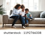 black family sitting on couch... | Shutterstock . vector #1192766338
