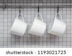 white coffee mugs hanging in...   Shutterstock . vector #1193021725