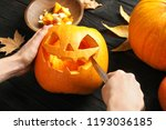 Woman Carving Halloween Pumpki...