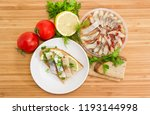 Stock photo top view of the open sandwich with slices of pickled atlantic herring fillet lemon and green onion 1193144998