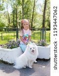 Stock photo beautiful little girl sitting on bench in park with her adorable white pomeranian dog 1193447062