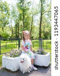 Stock photo beautiful little girl sitting on bench in park with her adorable white pomeranian dog 1193447065