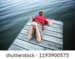 boy laying on a dock by a lake | Shutterstock . vector #1193900575