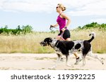 Stock photo woman runner running with dog on country road in summer nature fitness and exercising outdoors 119392225