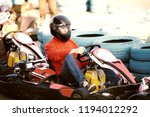 young man is driving go kart... | Shutterstock . vector #1194012292
