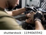 barber in black gloves trims... | Shutterstock . vector #1194065542