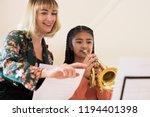 teacher helping female student... | Shutterstock . vector #1194401398