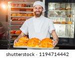 young handsome baker holding... | Shutterstock . vector #1194714442