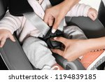mother fastening baby to child... | Shutterstock . vector #1194839185