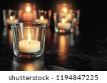 burning candle on table in... | Shutterstock . vector #1194847225