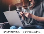 a woman holding and using... | Shutterstock . vector #1194883348