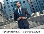 a young businessman fastens a... | Shutterstock . vector #1194913225