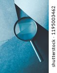 Small photo of magnifying glass. science research exploration and scrutiny concept. loupe on layered blue paper background.