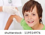 Happy boy receiving vaccine or injection - health professional in the background - stock photo
