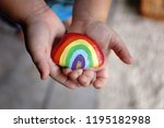 The hands of a young toddler child are gently holding an acrylic painted rainbow rock.