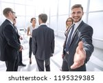 smiling businessman gives hand... | Shutterstock . vector #1195329385