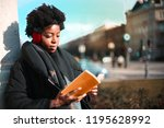 afro woman reading a book on... | Shutterstock . vector #1195628992