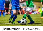 boys kicking football match on... | Shutterstock . vector #1195634548