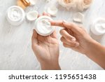 young woman applying body cream ... | Shutterstock . vector #1195651438