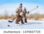 boys play hockey on a frozen... | Shutterstock . vector #1195837735