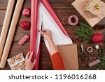 woman in a red sweater wrapping ... | Shutterstock . vector #1196016268