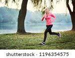 fit woman running during foggy...   Shutterstock . vector #1196354575
