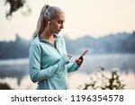 female runner seting up music... | Shutterstock . vector #1196354578