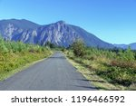 country road heading toward... | Shutterstock . vector #1196466592