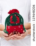Hands holding christmas present in a bag - stock photo