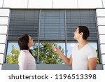 couple standing outside modern... | Shutterstock . vector #1196513398