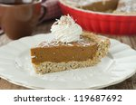 Piece of cake with pumpkin and chocolate, decorated with whipped cream and coconut - stock photo