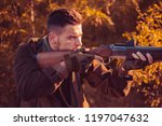 hunter with shotgun gun on hunt.... | Shutterstock . vector #1197047632