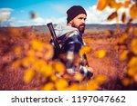 Autumn hunting season. Hunter with shotgun gun on hunt. Autunm hunting. Poacher with Rifle Spotting Some Deers. Close up Portrait of hamdsome Hunter - stock photo