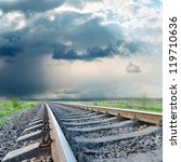 railroad to horizon under dramatic sky. rain before - stock photo