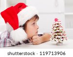 Boy looking at christmas tree made of gingerbread cookies - stock photo