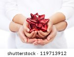 Holidays together concept - child and adult hands holding decorative bow, shallow depth - stock photo