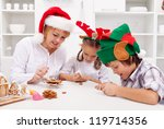 Happy christmas family decorating gingerbread cookies in the kitchen - stock photo