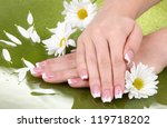 Woman hands with french manicure and flowers on green background - stock photo