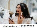 a gentle bride wears earrings... | Shutterstock . vector #1197237025