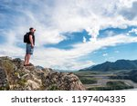 a man stands on the edge of a... | Shutterstock . vector #1197404335