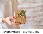 a young woman holding wrapped... | Shutterstock . vector #1197512482