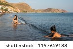Women and Teenager sitting on the beach in Greece
