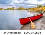Red Tandem Canoe With A Wooden...