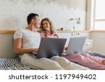 young couple sitting on bed in... | Shutterstock . vector #1197949402
