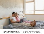 young couple sitting on bed in... | Shutterstock . vector #1197949408