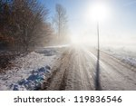Winter fog road with powerline post and direct sun - stock photo