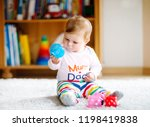 adorable baby girl playing with ... | Shutterstock . vector #1198419838