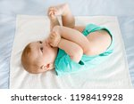 cute baby taking feet in mouth. ... | Shutterstock . vector #1198419928