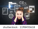 Small photo of Stressed young woman in checkered shirt sitting near chalkboard with electronic documents and internet icons. Concept of information overload. Toned image