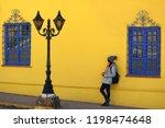 female leaning against vivid... | Shutterstock . vector #1198474648
